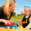 Stock Photo: Mother plays with child with toy car