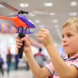 Boy in shop with toy helicopter - Stockfoto