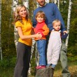 Parents with children in forest in autumn - Stock Photo