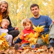 Stock Photo: Family with yellow maple leaves in wood in autumn