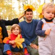 Family with yellow maple leaves in wood in autumn — Stock Photo