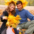 Pair and child with maple leaves in autumn wood - Foto Stock