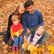 Family with yellow maple leaves in wood in autumn — Stock Photo #7447785