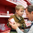 Grandfather and grandson choose conserve in food shop - Stock fotografie