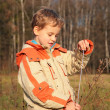 Boy in autumn wood with rope in hands - Stock Photo
