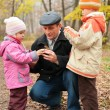 Grandfather with grandsons in forest in autumn — Stock Photo