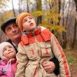 Grandfather with grandsons in forest in autumn look up — Stock Photo #7448689