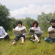 Four friends read newspapers on grass - Stock Photo