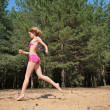 Young girl runs on sand in wood — Stockfoto