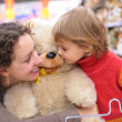 Mother with daughter and soft toy - Stock Photo