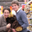 Couple in shop with big soft toy — Stock Photo