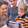 Boy with parents with toy in shop - Stock Photo