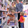 Family with son in cart in shop - Stock Photo