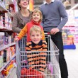 Parents with children in cart in shop — Foto Stock #7449462
