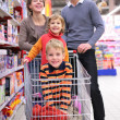 Parents with children in cart in shop — Stock Photo