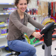 Young woman on sports training apparatus in shop — Stock Photo #7449494