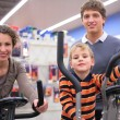 Parents with son on sports training apparatus in shop — Stock Photo
