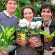 Three friends in shop holds pots with plants in shop — Stock Photo #7449514