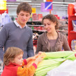 Parents with  child choose  fabric in shop — Stok fotoğraf