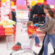 Parents roll cart with child in supermarket - Stock Photo