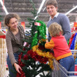 Family buys Christmas-tree with decorations — Stock Photo #7449527