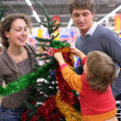 Parents with child buys Christmas-tree with decorations — Stock Photo #7449530
