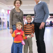 Parents with children in supermarket - Stock Photo