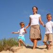 Mother with children goes on sand — Stock Photo