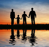 Family of four on sunset sky, water — Stock Photo