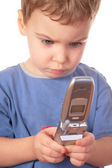 Little girl looks on cell phone — Stock Photo