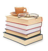 Coffee cup and glasses on pile of book — Stock Photo