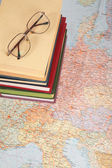Glasses on pile of books on map of europe — Stock Photo