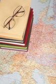 óculos na pilha de livros no mapa da europa — Fotografia Stock