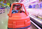 Children in toy automobile in supermarket 3 — Stock Photo