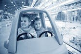 Children in toy automobile in supermarket — Stock Photo