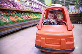 Children in toy automobile in store — Stock Photo
