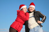 Couple against blue sky background in winter in santa claus hats — Fotografia Stock