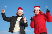 Couple against blue sky background in winter in santa claus hats with spark — Stock Photo