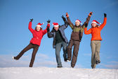 Four friends jump on top of snow hill in santa claus hats — Stock Photo