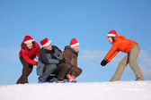 One woman pull two men on sled, other woman push them — Stock Photo