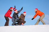 One woman pull two men on sled, other woman push them 2 — Stock Photo