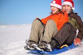 Homme et femme en chapeaux de père noël ride sur traîneau — Photo