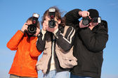 Three photographers against blue sky — Stock Photo