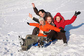 Group of friends sit on plastic sled on snow — Stock Photo