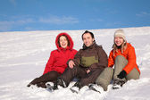 Three friends sit on snow on hillside — Stockfoto