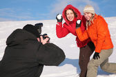 Two girls throw snows into photographer — Stock Photo