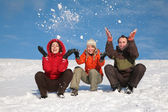 Three friends sit on snow and throw snows — Stock Photo