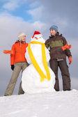Pareja con muñeco de nieve con sombrero de santa claus — Foto de Stock