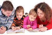 Los padres con el hijo y la hija miren libros 2 — Foto de Stock
