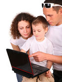 Parents whit son look on notebook — Stok fotoğraf